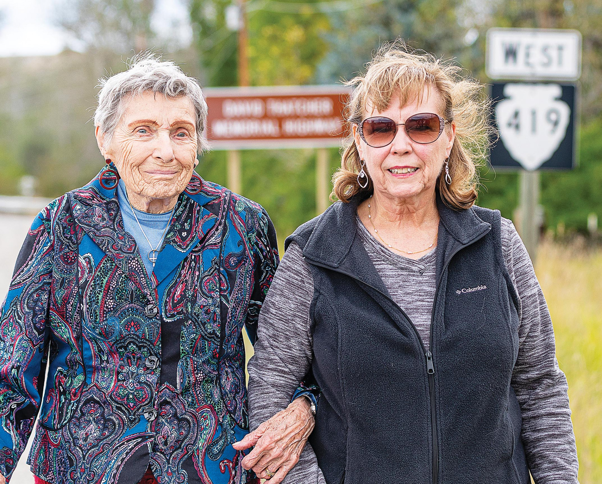 Photo by Maurice CravensThatcher's wife and daughter — Dawn Thatcher and Sandy Miller — pose in front of the new highway sign.