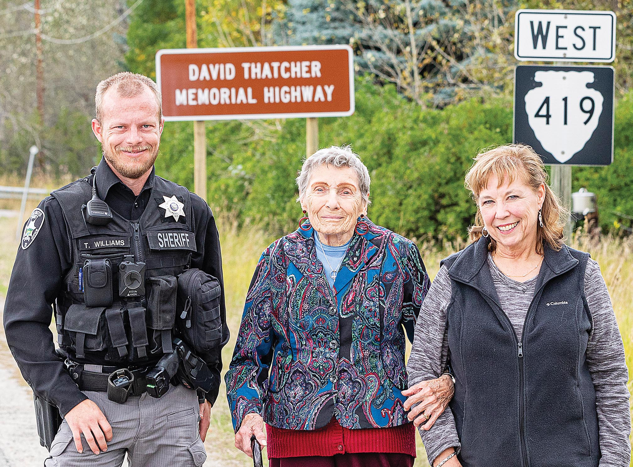 Photo by Maurice CravensStillwater County Sheriff's Deputy Ty Williams poses with Thatcher's wife and daughter — Dawn Thatcher and Sandy Miller —  in front of the new highway sign.