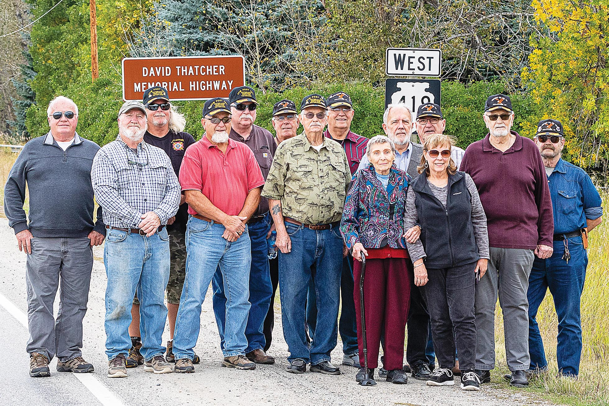 Photo by Maurice CravensVFW Post 7311 members pose in front of the new highway sign with members of David Thatcher's family.